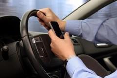 Via la patente a chi guida con smartphone